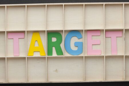 Word target made of colorful alphabet letters on wooden surface. 스톡 콘텐츠