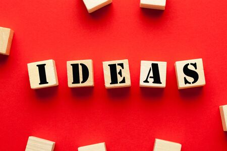 Word Ideas written on cubes shape wooden blocks on red background. Business Concept.