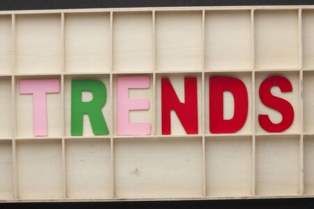 The word Trends spelled with colorful alphabet letters on wooden surface.