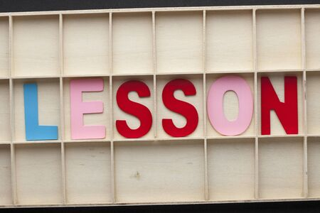 The word Lesson spelled with colorful alphabet letters on wooden surface.