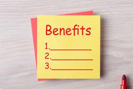 Benefits list written on note with marker pen on a wooden desk.