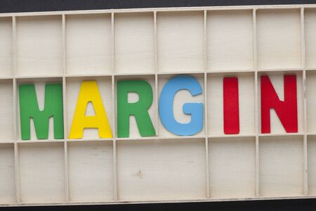 The word Margin spelled with colorful alphabet letters on wooden surface. 写真素材