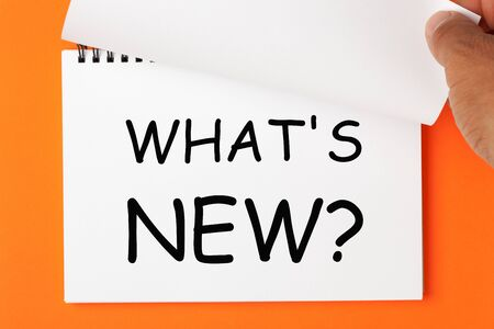 Whats New question written on a notebook. Hand turn page. Business concept.