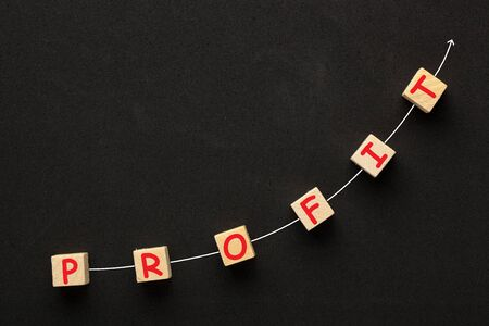 The word Profit on cubes shape wooden blocks with directional arrow on black background.