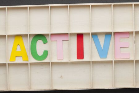 The word active spelled with colorful alphabet letters on wooden surface. 写真素材