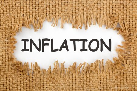 Piece of burlap with hole with the word inflation. Business concept.