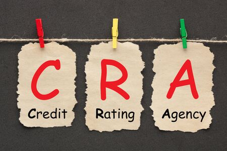 Credit Rating Agency (CRA) written on set stickers with clip hanging on a rope on black background. Business acronyms