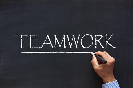 Men hand writing word Teamwork with chalk marker on blackboard. Business concept.