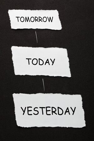 Yesterday Today Tomorrow text on 3 piece of torn paper over black surface.