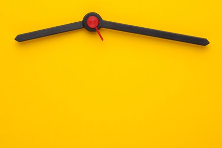 Hour hand, minute hand and a red second on yellow dial of the clock. Copy space for text.