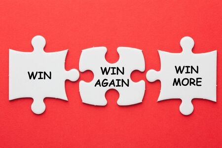 Win, Win Again and Win More text on 3 pieces paper puzzle on a red background. Business concept. 写真素材