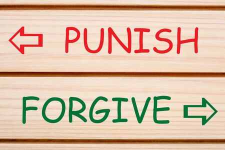 Opposite words Punish or Forgive written on wood wall decor. Stock Photo