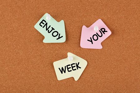 Enjoy Your Week text on color reminder notes with pin on cork board. Business concept