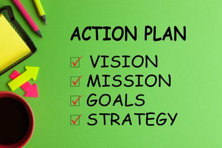 Action Plan list with conceptual words, cup of coffee and office supplies on green background.