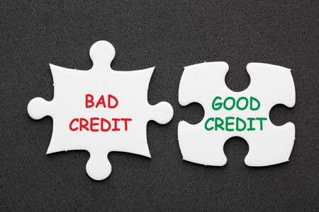 Good Credit vs Bad Credit text in 2 pieces paper puzzle on black background. Business concept. 写真素材