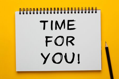 The phrase Time For You written on notepad with pencil on yellow background.