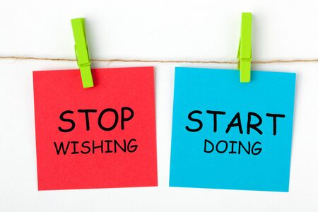 The phrase Stop Wishing Start Doing written on color notes with wooden pinch.