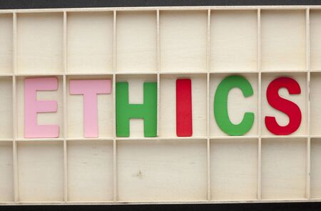 The word Ethics spelled from colored wooden letters on wooden surface. Business Concept.
