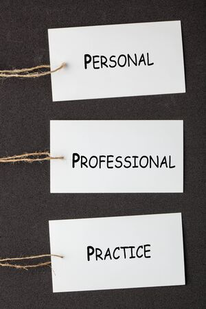 The words Personal, Professional and Practice written on paper labels set on black background. Business concept 写真素材
