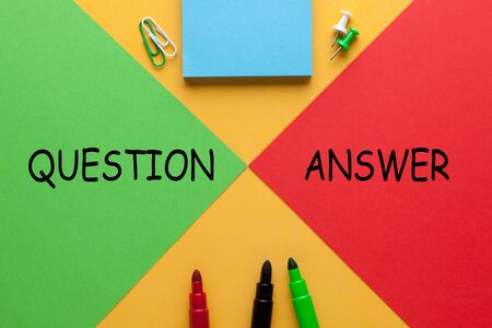 The words Question and Answer on red vs. green triangle with various stationery.