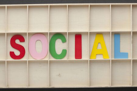 The word Social spelled from colored wooden letters on wooden surface. Business Concept.