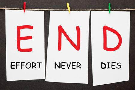 Effort Never Dies (END) written on set stickers with clip hanging on a rope on black background.