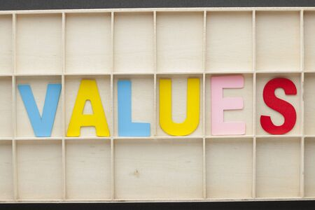 Word Values made of colorful alphabet letters on wooden surface.