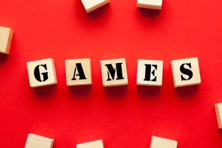 The word Games written on cubes shape wooden blocks on red background.