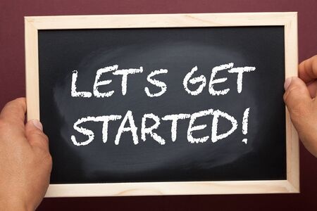 Hands holding blackboard with phrase Lets Get Started. Business concept
