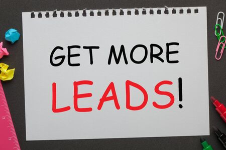 Get More Leads text on notebook paper and office supplies on black background.