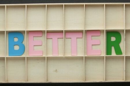 The word Better made of colorful alphabet letters on wooden surface.