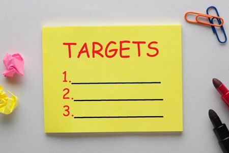 Targets blank list on note with marker pen and various stationery. Business concept.
