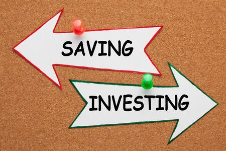 The words Saving vs. Investing written on paper arrow pinned on cork board. Business concept 写真素材