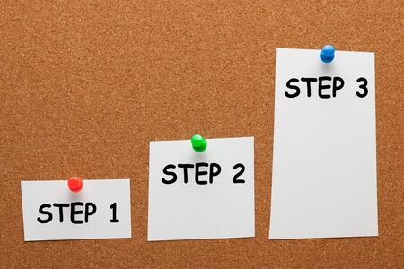 The words Step 1 Step 2 Step 3 written on paper sheet with pin in the shape of a staircase on cork board. Business concept.