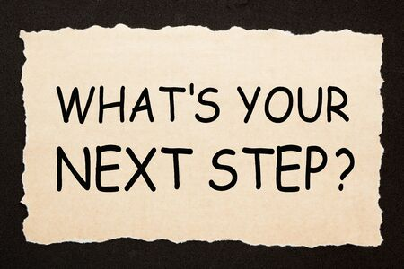 Whats Your Next Step question on old torn paper on black background. Business concept.