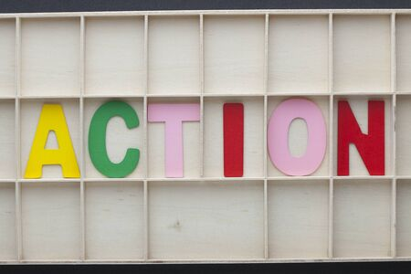 The word Action made of colorful alphabet letters on wooden surface.