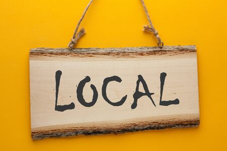 The word Local written in watercolor over a wooden sign hanging on a rope on a yellow background.