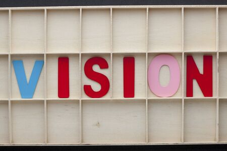 The word Vision made of colorful alphabet letters on wooden surface.