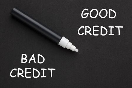 The words Good Credit vs Bad Credit written with white marker on black background. Stockfoto