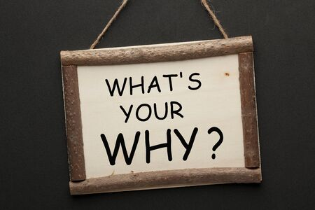 What's Your Why question on wooden sign hanging on a rope on black background. Stockfoto - 129226805