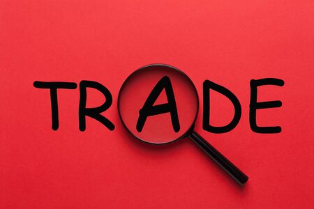 The word Trade under magnifying glass on red background. Zdjęcie Seryjne