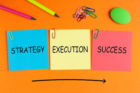 Strategy Execution Success text on notes pasted on orange background with a big arrow and office supplies.