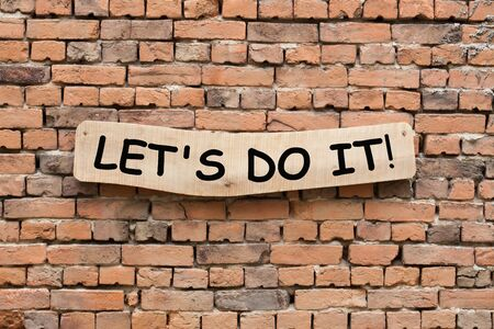 Lets Do It phrase on wooden sign on brick wall background.  Motivation concept
