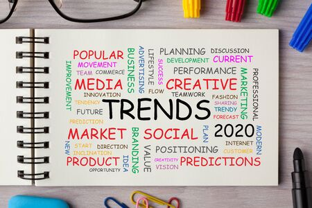 Word cloud concept of trends 2020 on notebook page with marker pen and various stationery.