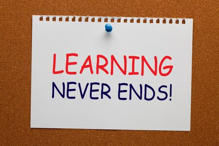 Learning Never Ends text on white notebook paper pinned on cork board. Business concept