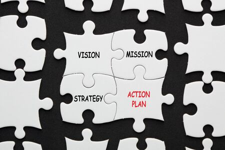 Vision, mission, strategy and action plan written in 4 piece puzzle on black background. Business concept.