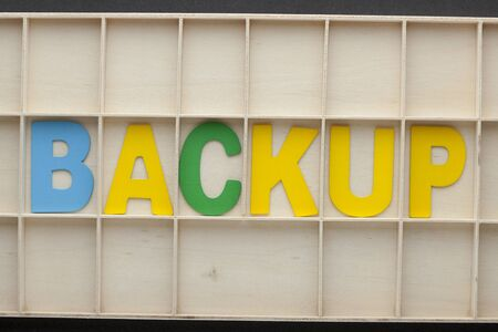 The word backup made of colorful alphabet letters on wooden surface.