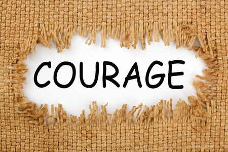 Piece of burlap with hole with the word courage. Business concept. Stock fotó