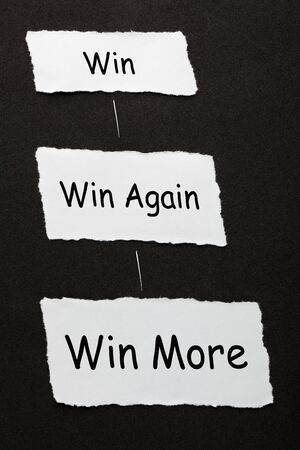 Win, Win Again and Win More text on 3 piece of torn paper over black surface.