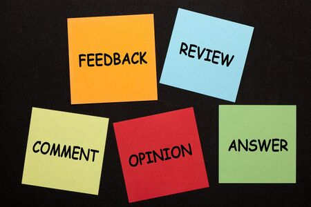 Feedback, review, comment, opinion or answer text on colorful notes on black background.